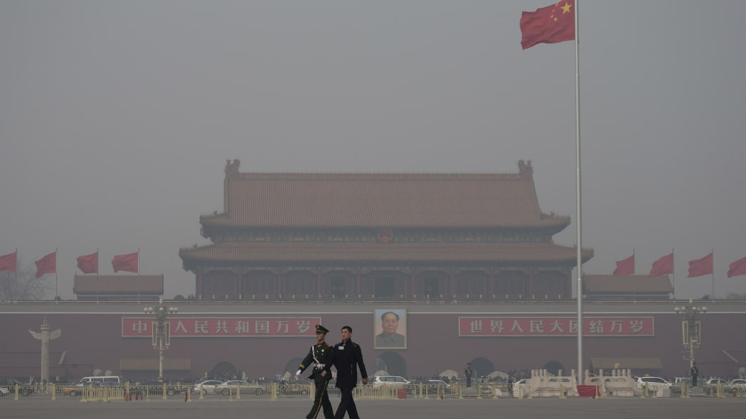 China Environment Vs Economy (In this Friday, March 8, 2013 Chinese paramilitary policemen march across Tiananmen Square on a hazy day in Beijing, China. Facing public outrage over smog-choked cities