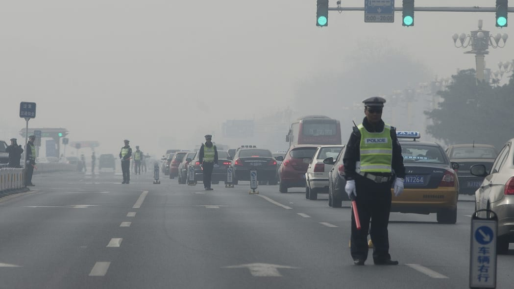 China Environment Vs Economy (In this Thursday, March 7, 2013 Chinese traffic policemen closed off a road for delegation buses attending the annual Chinese People's Political Consultative Conference h