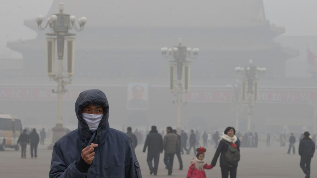Japan China Smog (FILE - In this Tuesday, Jan. 29, 2013 file photo, a man wears a mask on Tiananmen Square in thick haze in Beijing. Japan's Foreign Ministry says it is seeking to cooperate and exchan