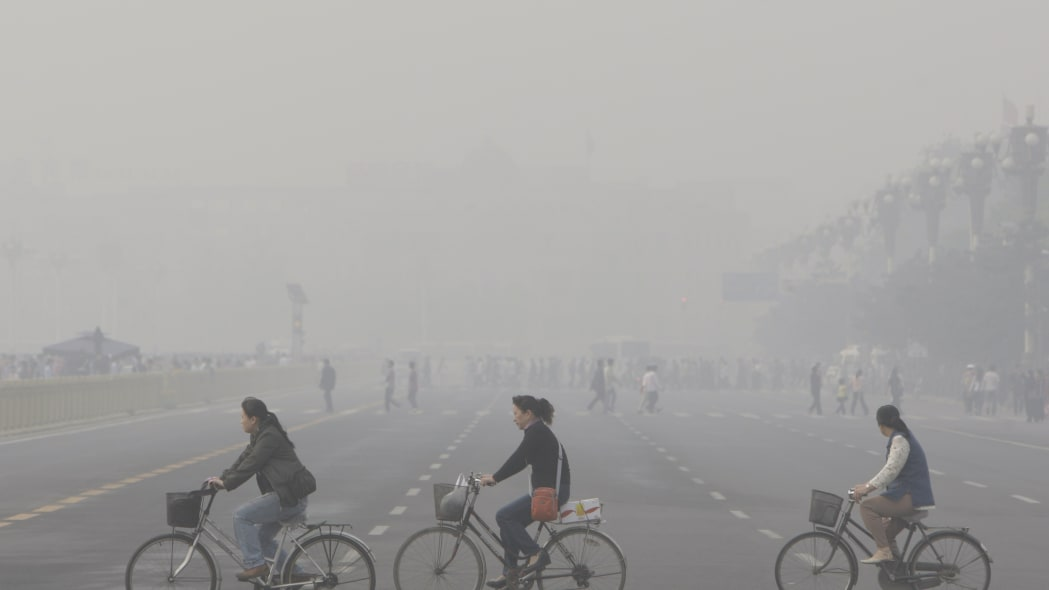 China Olympia (** FILE ** Chinese cycle through smog and pollution over Beijing's Tiananmen Square Thursday , May 1, 2008. Beijing's Olympic shutdown begins Sunday, July 20, 2008, a drastic plan to li