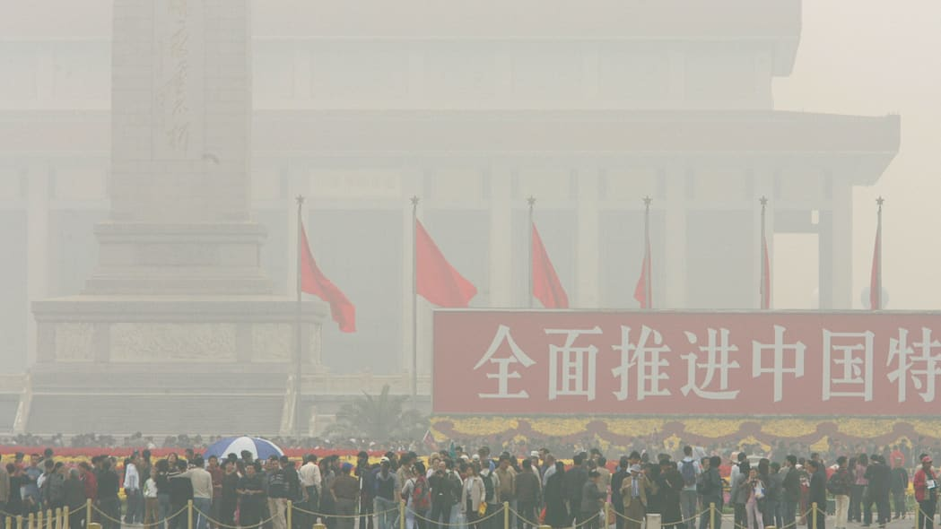 CHINA SMOG CRACKDOWN (** FILE ** Visitors walk through haze hanging over Beijing's Tiananmen Square in this Oct. 10, 2004 file photo. Shougang, a major Chinese steelmaker, has been told to cut output