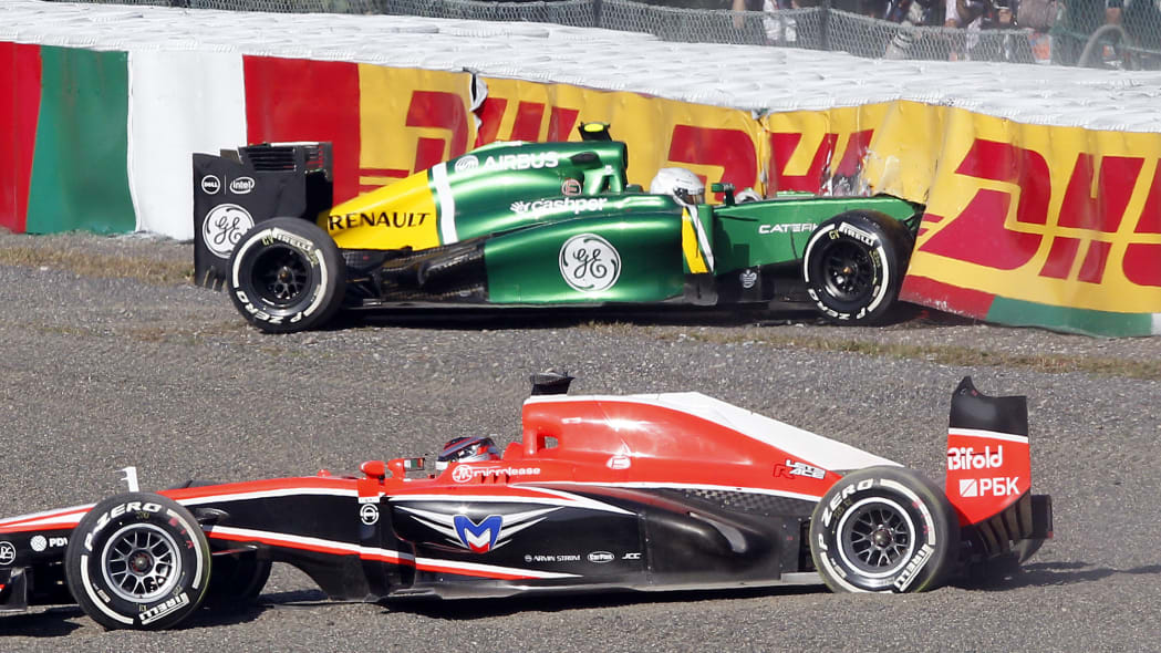 Japan F1 GP Auto Racing (Marussia driver Jules Bianchi, front, and Caterham driver Giedo van der Garde of the Netherlands sit in their cars after crashing at the start of the Japanese Formula One Gran