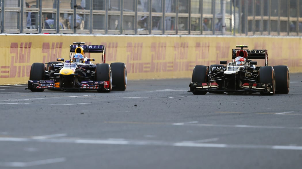 Japan F1 GP Auto Racing (Red Bull driver Sebastian Vettel of Germany, left, and Lotus driver Romain Grosjean of France race side by side during the Japanese Formula One Grand Prix at the Suzuka circui