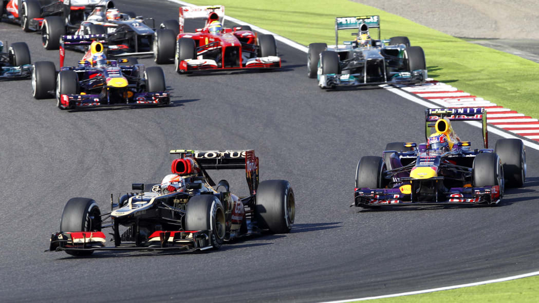 Japan F1 GP Auto Racing (Lotus driver Romain Grosjean of France, left, leads Red Bull driver Mark Webber of Australia into turn 2 at the start of the Japanese Formula One Grand Prix at the Suzuka circ