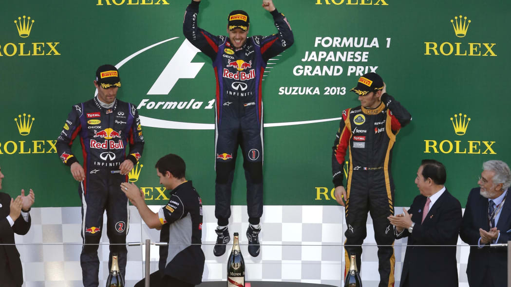 Japan F1 GP Auto Racing (Red Bull driver Sebastian Vettel of Germany, center,  jumps on the podium as he celebrates after winning the Japanese Formula One Grand Prix at the Suzuka circuit in Suzuka, J