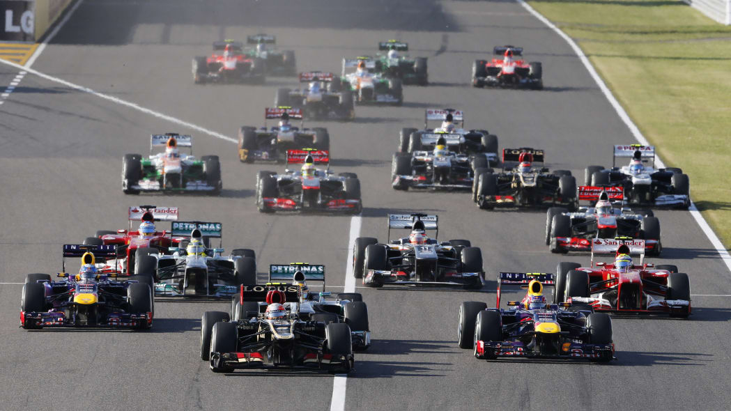 Japan F1 GP Auto Racing (Lotus driver Romain Grosjean of France, center, leads Red Bull driver Mark Webber of Australia, front right, and Red Bull driver Sebastian Vettel of Germany, left, at the star