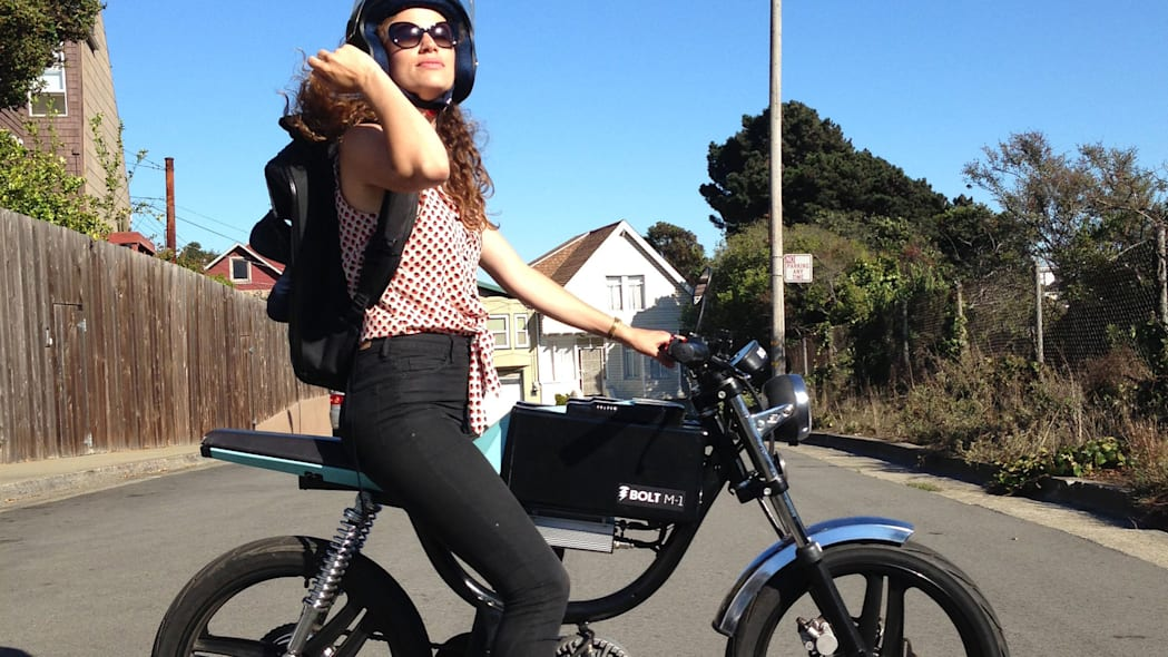 Bolt Motorbikes M-1 electric moped on the street with female rider