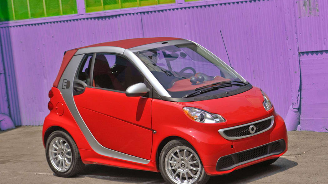 all-electric Smart ED in red by purple wall