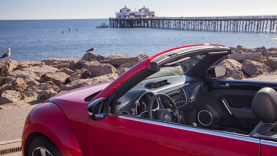 VW Beetle convertible in red by a pier at the ocean