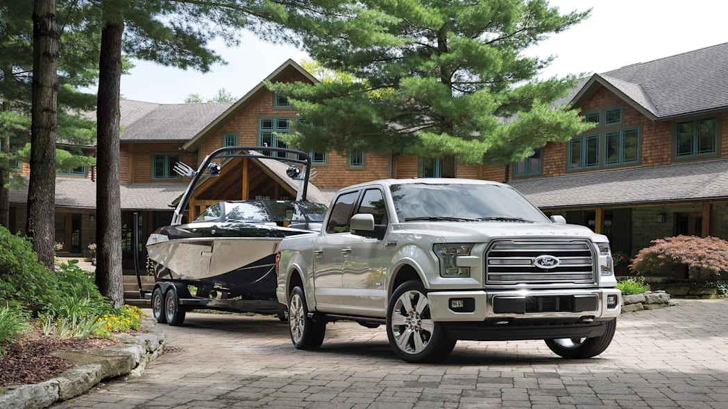 The 2016 Ford F-150 Limited towing a boat, front three-quarter view.