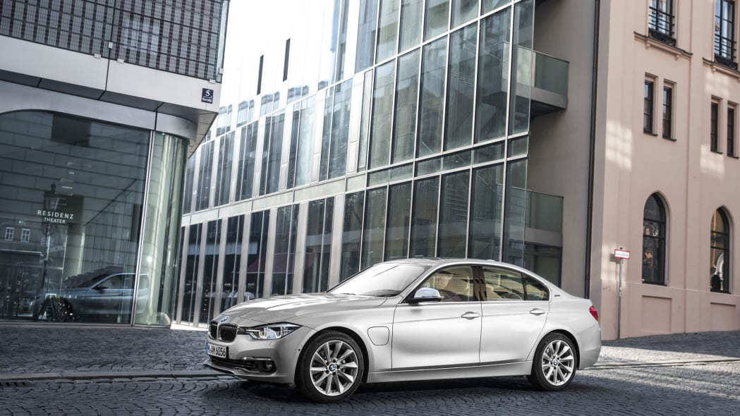bmw 330e driving by glass