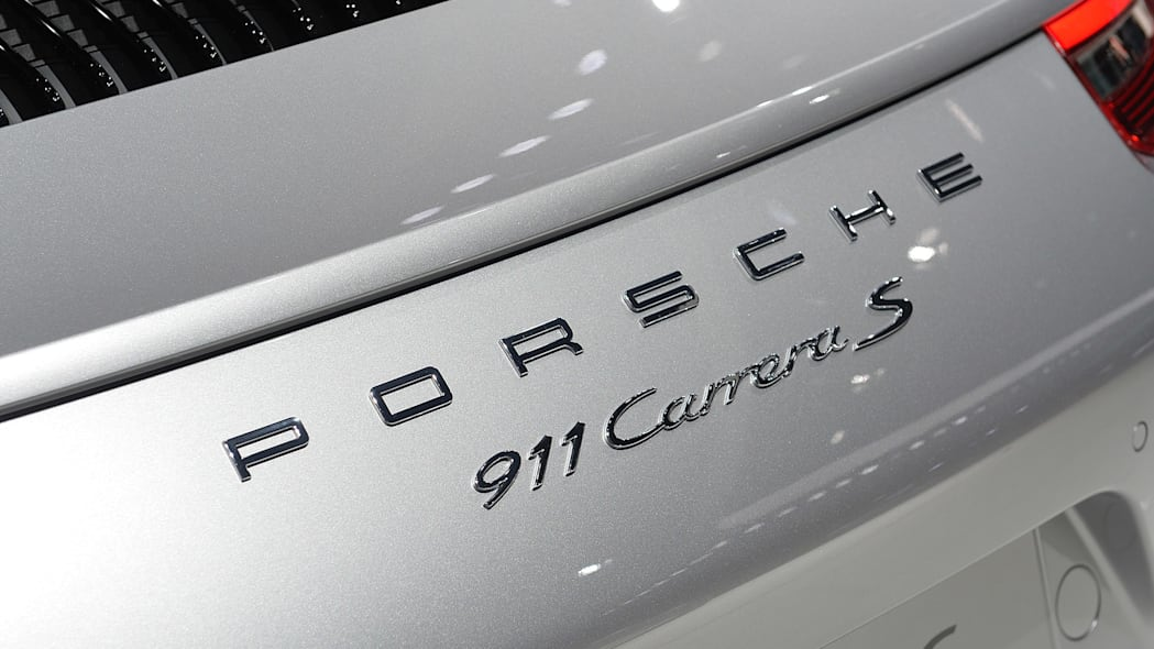 The 2016 Porsche 911 Carrera, now with a turbocharged engine in the standard car, unveiled at the Frankfurt Motor Show, hood cover badge detail.