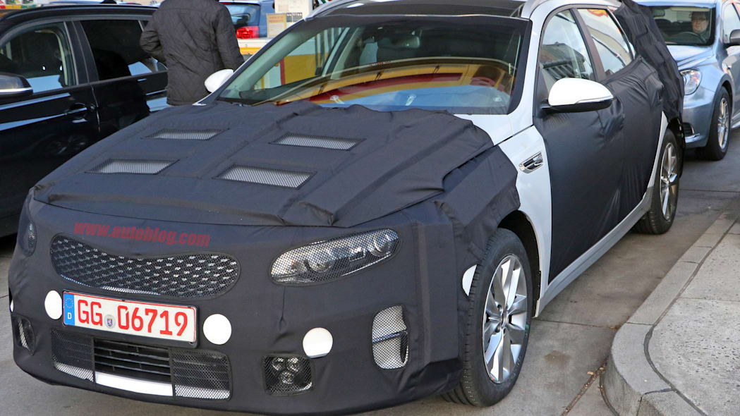 Kia Sportswagon prototype caught by spy photographers, front three-quarter at a gas station.