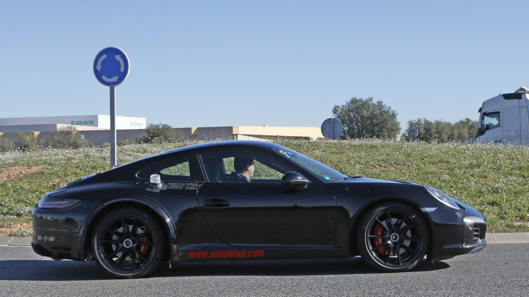 Spy shot of the next-generation 992-model Porsche 911 thought to hide a hybrid powertrain, side.
