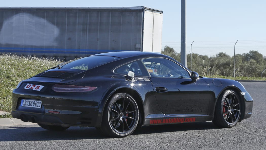 Spy shot of the next-generation 992-model Porsche 911 thought to hide a hybrid powertrain, rear three-quarter.