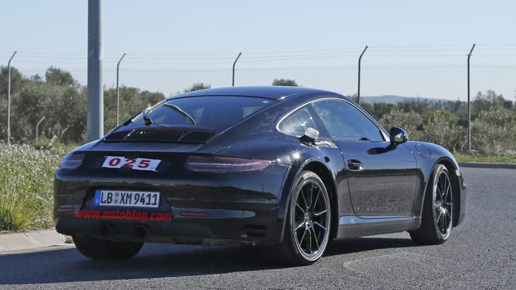 Spy shot of the next-generation 992-model Porsche 911 thought to hide a hybrid powertrain, rear three-quarter. The rear fender flares hide a wider rear axle.