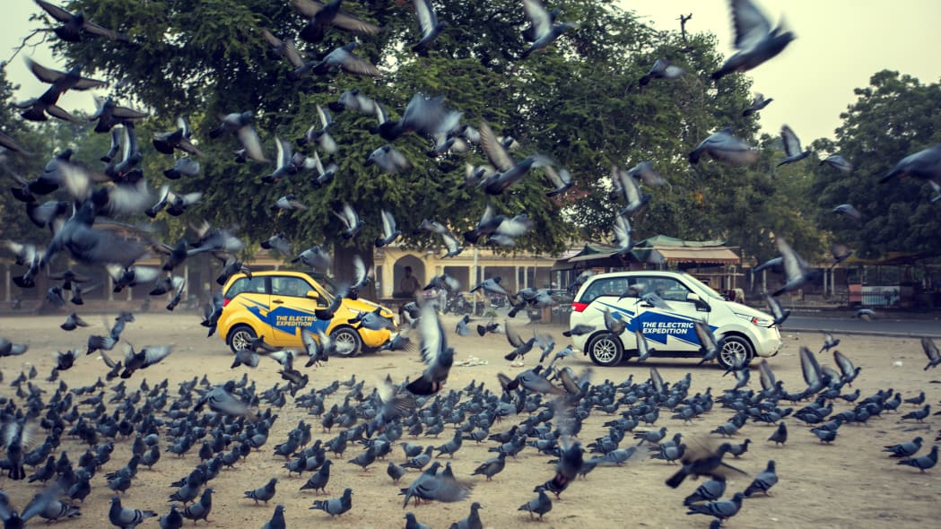 Two REVA EVs startle pigeons during the Mahindra Electric Expedition.