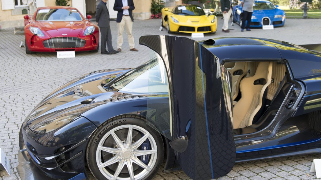 People looking at a 2015 Koenigsegg One:1 model car in front of a Aston Martin One-77 Coupe (2011), red, Ferrari LaFerrari (2015), yellow, and a Bugatti Veyron EB 16.4 Coupe (2010), blue, part of some 25 luxury cars owned by Teodoro Obiang, the son of the Equatorial Guinea's President Teodoro Obiang Nguema Mbasogo are pictured before an auction of sales house Bonhams at the Bonmont Abbey Golf & Country Club in Cheserex near Geneva, Switzerland, Sunday, September 29, 2019. A collection of luxury cars from Equatorial Guinea's vice president Teodorin Obiang Nguema confiscated by the Geneva prosecutor's office after a deal ending a money-laundering inquiry, are auctioned off in Switzerland and are estimated to bring in 18.5 million Swiss francs. (Laurent Gillieron/Keystone via AP)