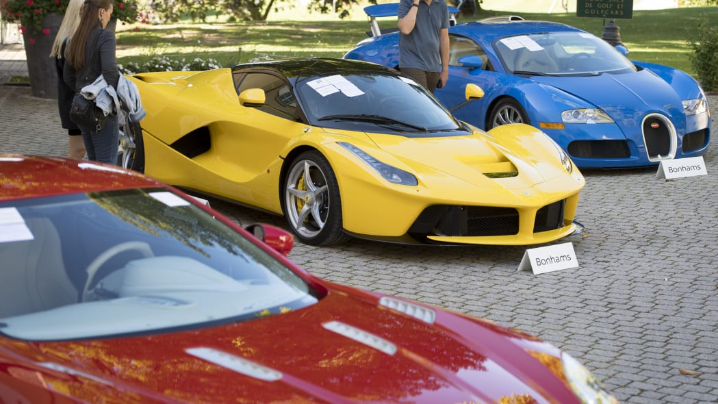 People looking at a Aston Martin One-77 Coupe (2011) in front of a Ferrari LaFerrari (2015), yellow, and a Bugatti Veyron EB 16.4 Coupe (2010), blue, part of some 25 luxury cars owned by Teodoro Obiang, the son of the Equatorial Guinea's President Teodoro Obiang Nguema Mbasogo are pictured before an auction of sales house Bonhams at the Bonmont Abbey Golf & Country Club in Cheserex near Geneva, Switzerland, Sunday, Sept. 29, 2019. A collection of luxury cars from Equatorial Guinea's vice president Teodorin Obiang Nguema confiscated by the Geneva prosecutor's office after a deal ending a money-laundering inquiry, are auctioned off in Switzerland and are estimated to bring in 18.5 million Swiss francs. (Laurent Gillieron/Keystone via AP)