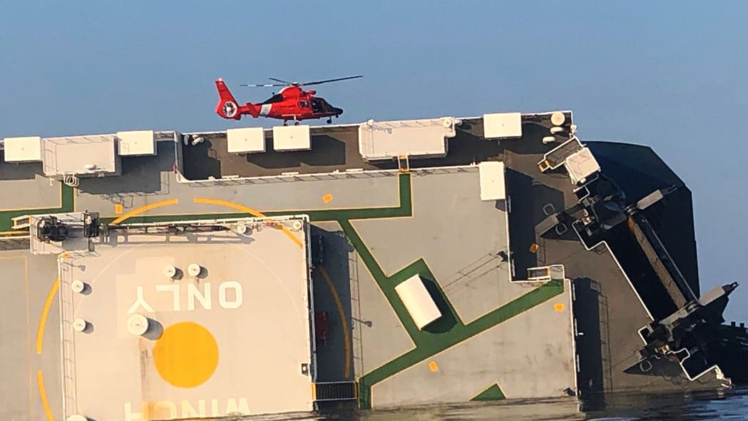 In this image released by the U.S. Coast Guard, a USCG helicopter hovers over an overturned cargo ship in St. Simons Sound, Ga., Monday, Sept. 9, 2019. The U.S. Coast Guard says rescuers have heard noises from inside the ship where multiple crew members are missing after their huge vessel overturned and caught fire off Georgia's coast.   (U.S. Coast Guard via AP)
