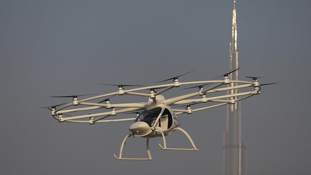 In this Sept. 26, 2017 photo, a Volocopter prototype flies in front of the Burj Khalifa, the world's tallest tower, during a test flight in Dubai, United Arab Emirates. Dubai is hoping to one day have flying, pilotless taxis darting among its skyscrapers. Just this week, the city-state in the United Arab Emirates hosted crews from the German company Volocopter, which had an electric, battery-powered two-seat prototype take off and land. Dubai hopes to have rules in place in the next five years to be ready for having the aircraft regularly flying through its skies. (AP Photo/Kamran Jebreili)