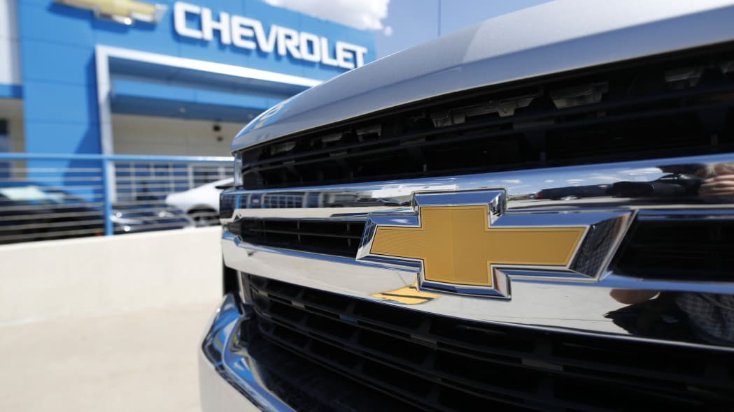FILE--In this Sunday, July 28, 2019, file photograph, the company logo shines off the grille of an unsold 2019 Chevrolet Silverado pickup truck at a dealership in Englewood, Littleton, Colo. (AP Photo/David Zalubowski, File)