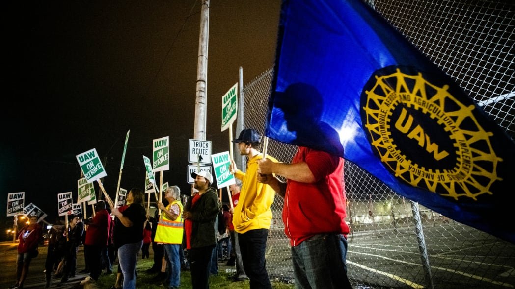 Davison resident Jeff Elkins, 37 years old, and a General Motors employee who works on the line, waves a United Auto Workers flag as employees leave the Flint Assembly Plant at midnight as part of the national strike on Monday, Sept. 16, 2019, in Flint, Michigan. More than 49,000 members of the United Auto Workers walked off General Motors factory floors or set up picket lines early Monday as contract talks with the company deteriorated into a strike. (Jake May/The Flint Journal via AP)