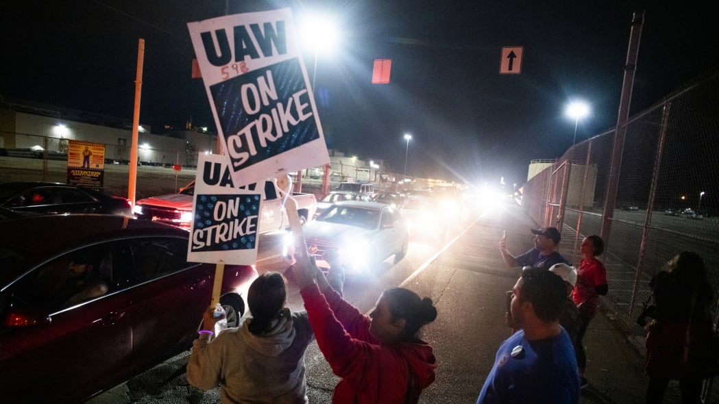 Hundreds of General Motors employees drive off the property, shutting down the Flint Assembly Plant at midnight as part of the national strike on Monday, Sept. 16, 2019 in Flint, Michigan. (Jake May/The Flint Journal via AP)