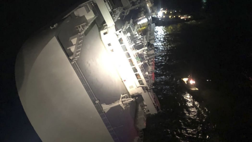 In this photo provided by the U.S. Coast Guard, the Golden Ray cargo ship lists to one side near a port on the Georgia coast, early Sunday, Sept. 8, 2019. The ship, carrying vehicles, was being evacuated after sharply listing. The U.S. Coast Guard said the vessel was leaving Brunswick when it somehow turned drastically sideways early Sunday. (U.S. Coast Guard via AP)
