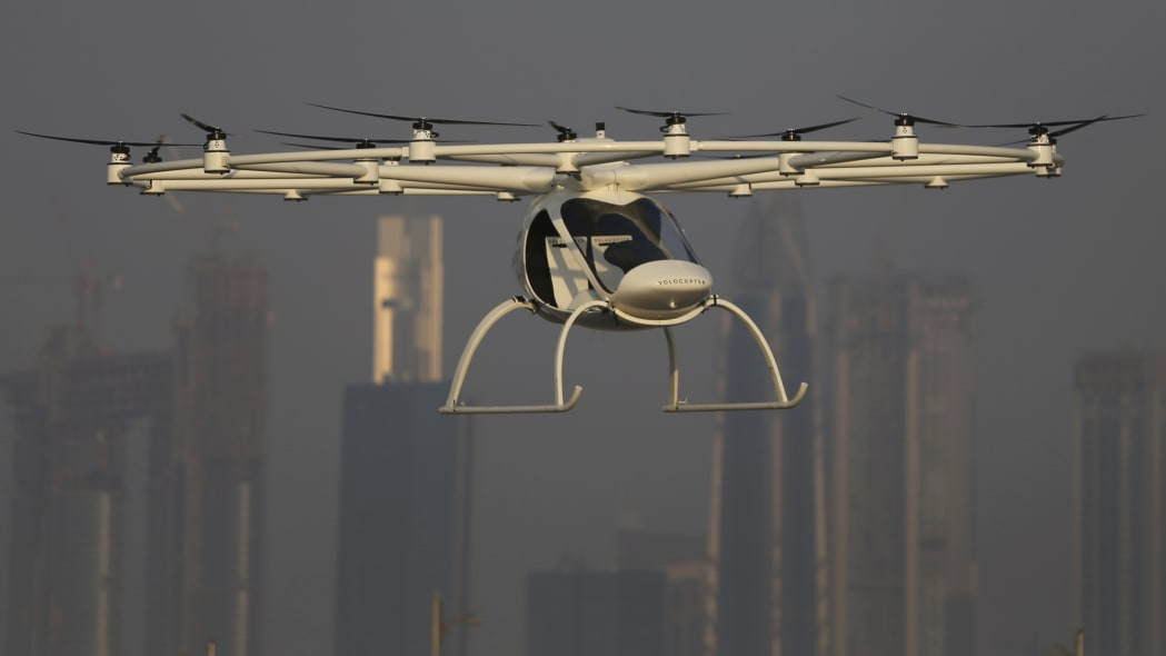 In this Sept. 26, 2017 photo, a Volocopter prototype flies in front of the city skyline during a test flight in Dubai, United Arab Emirates. Dubai is hoping to one day have flying, pilotless taxis darting among its skyscrapers. Just this week, the city-state in the United Arab Emirates hosted crews from the German company Volocopter, which had an electric, battery-powered two-seat prototype take off and land. Dubai hopes to have rules in place in the next five years to be ready for having the aircraft regularly flying through its skies. (AP Photo/Kamran Jebreili)