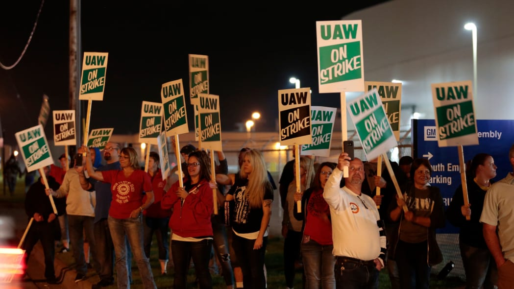 Members of the United Auto Workers (UAW) who are employed at the General Motors Co. Flint Assembly plant in Flint, Michigan, hold signs and react as workers drive out of the plant as they go on strike early on September 16, 2019. - The United Auto Workers union began a nationwide strike against General Motors on September 16, with some 46,000 members walking off the job after contract talks hit an impasse. (Photo by JEFF KOWALSKY / AFP)        (Photo credit should read JEFF KOWALSKY/AFP/Getty Images)