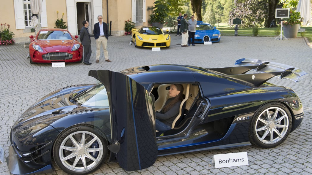 People looking at a 2015 Koenigsegg One:1 model car in front of a Aston Martin One-77 Coupe (2011), red, Ferrari LaFerrari (2015), yellow, and a Bugatti Veyron EB 16.4 Coupe (2010), blue, part of some 25 luxury cars owned by Teodoro Obiang, the son of the Equatorial Guinea's President Teodoro Obiang Nguema Mbasogo are pictured before an auction of sales house Bonhams at the Bonmont Abbey Golf & Country Club in Cheserex near Geneva, Switzerland, Sunday, Sept. 29, 2019. A collection of luxury cars from Equatorial Guinea's vice president Teodorin Obiang Nguema confiscated by the Geneva prosecutor's office after a deal ending a money-laundering inquiry, are auctioned off in Switzerland and are estimated to bring in 18.5 million Swiss francs. (Laurent Gillieron/Keystone via AP)