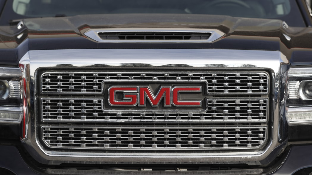 In this Sunday, Nov. 10, 2019, photograph, the company logo shines off the grille of an unsold 2020 Sierra pickup truck at a GMC dealership in Littleton, Colo. (AP Photo/David Zalubowski)