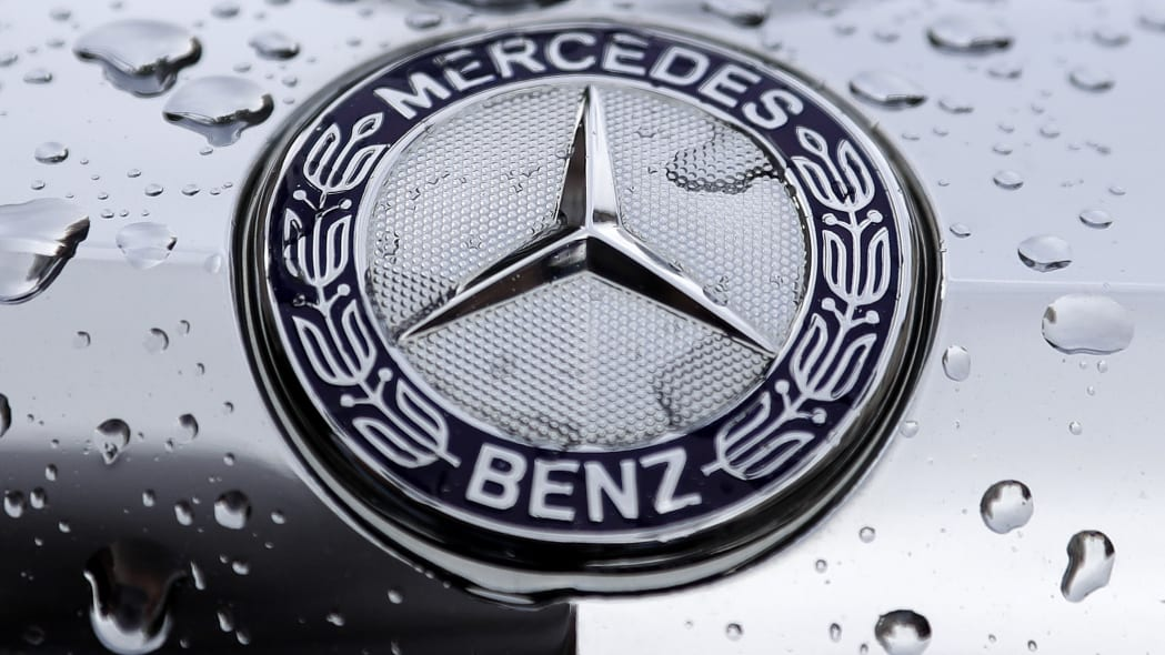 The logo of German car manufacturer Mercedes-Benz is rain covered at a car in Munich, Germany, Friday, July 28, 2017. (AP Photo/Matthias Schrader)