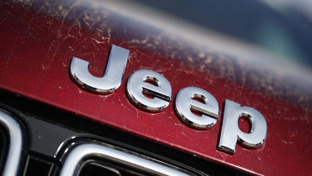 In this Sunday, April 15, 2018, photograph, the company logo shines on the leading edge of a hood of an unsold 2018 Grand Cherokee on a Jeep dealer's lot in the south Denver suburb of Englewood, Colo. (AP Photo/David Zalubowski)