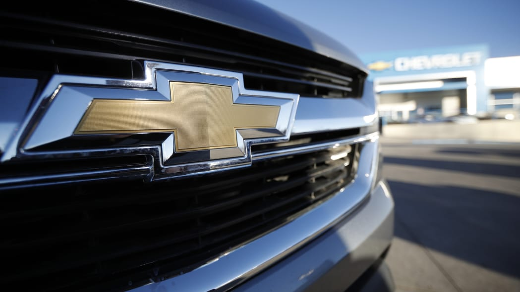 In this Sunday, Feb. 3, 2019, file photograph, the corporate bowtie logo gleams off the grille of an unsold 2019 Colorado pickup as it sits at a Chevrolet dealership in Littleton, Colo. (AP Photo/David Zalubowski)