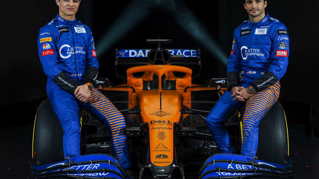 IMAGE DISTRIBUTED FOR MCLAREN - McLaren drivers Lando Norris, left, and Carlos Sainz, sit either side of McLaren's new 2020 Formula 1 car, the MCL35, unveiled at the McLaren Technology Centre on Thursday, Feb. 13, 2020, in Woking, United Kingdom. Press release and full launch media assets available to download at http://www.apmultimedianewsroom.com/multimedia-newsroom/mclaren-reveals-the-mcl35-to-the-world. (Zak Mauger/McLaren via AP Images)