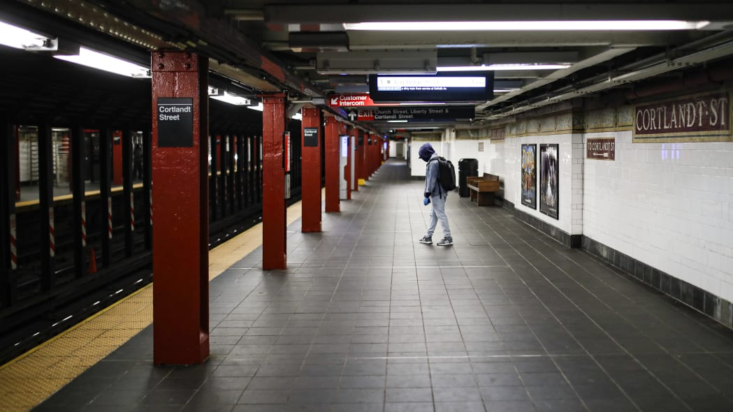 A subway customer wears protective gloves and a face mask due to COVID-19 concerns while walking along an empty train platform at the Cortlandt Street station, Saturday, March 21, 2020, in the Brooklyn borough of New York. New York Gov. Andrew Cuomo announced sweeping orders Friday that will severely restrict gatherings of any size for the state's more than 19 million residents and will require workers in nonessential businesses to stay home. (AP Photo/John Minchillo)