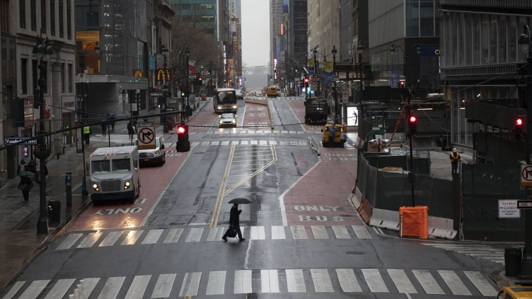 A commuter crosses 42nd Street in front of Grand Central Terminal during morning rush hour, Monday, March 23, 2020, in New York. Gov. Andrew Cuomo has ordered most New Yorkers to stay home from work to slow the coronavirus pandemic. (AP Photo/Mark Lennihan)