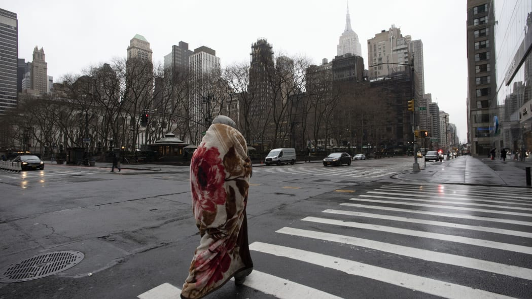 A man wrapped in a blanket crosses 42nd Street at Sixth Avenue, which is usually a very busy pedestrian intersection on a weekday morning, Monday, March 23, 2020 in New York. Gov. Andrew Cuomo has ordered most New Yorkers to stay home from work to slow the coronavirus pandemic. (AP Photo/Mark Lennihan)