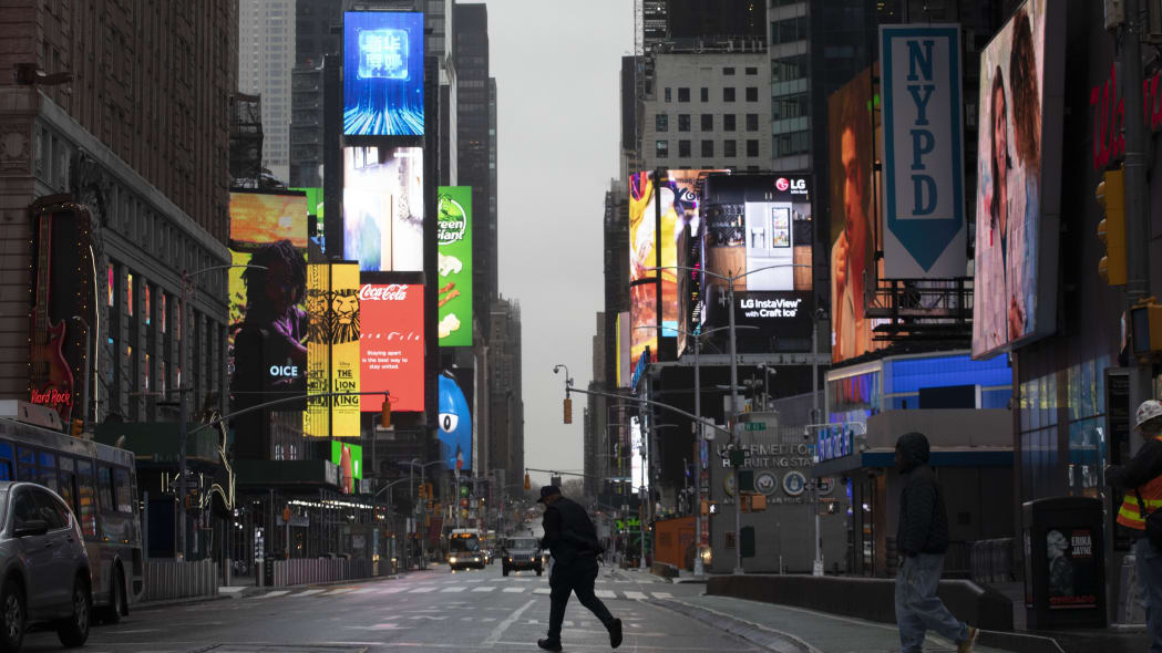 A man walks through a nearly empty Times Square, which is usually very crowded on a weekday morning, Monday, March 23, 2020 in New York. Gov. Andrew Cuomo has ordered most New Yorkers to stay home from work to slow the coronavirus pandemic. (AP Photo/Mark Lennihan)