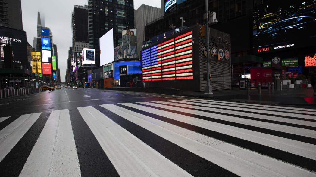 Times Square, which is usually very crowded on a weekday morning, is mostly empty Monday, March 23, 2020 in New York. Gov. Andrew Cuomo has ordered most New Yorkers to stay home from work to slow the coronavirus pandemic. (AP Photo/Mark Lennihan)