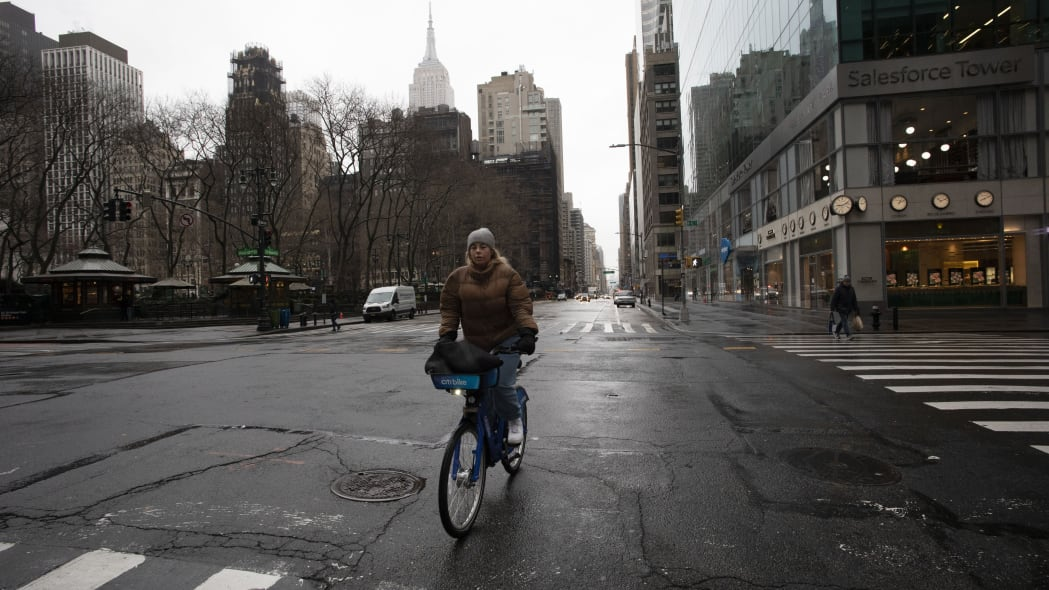 A woman cycles up Sixth Avenue, Monday, March 23, 2020 in New York. Gov. Andrew Cuomo has ordered most New Yorkers to stay home from work to slow the coronavirus pandemic. (AP Photo/Mark Lennihan)