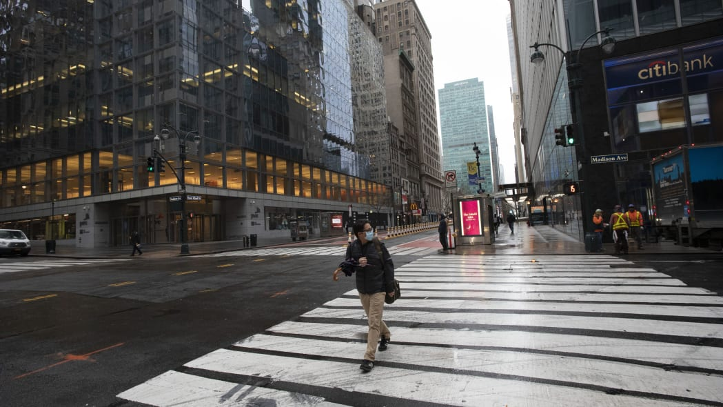 A commuter crosses Madison Ave., Monday, March 23, 2020 in New York. Gov. Andrew Cuomo has ordered most New Yorkers to stay home from work to slow the coronavirus pandemic. (AP Photo/Mark Lennihan)