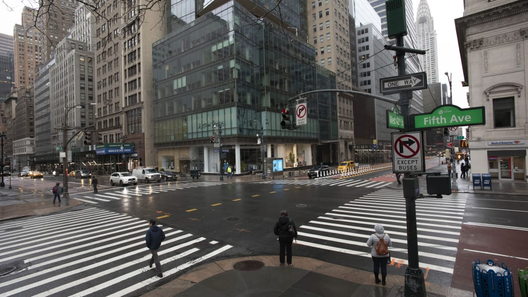 Commuters are in the intersection of Fifth Ave. and 42nd Street, which is normally very crowded on a weekday morning, Monday, March 23, 2020 in New York. Gov. Andrew Cuomo has ordered most New Yorkers to stay home from work to slow the coronavirus pandemic. (AP Photo/Mark Lennihan)