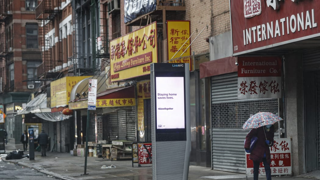 A lone pedestrian walks down the Bowery while wearing a protective mask and glass as a sign urging people to remain home due to coronavirus concerns is displayed, Monday, March 23, 2020, in New York. (AP Photo/John Minchillo)