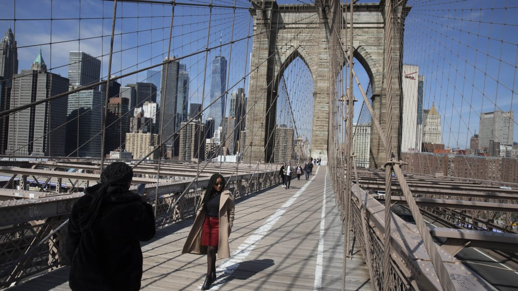Ines Tshiyomba, center, poses as her friend Garethe Mawonso takes her photo on the Brooklyn Bridge, Monday, March 16, 2020 in New York. The Parisians are stuck in New York for another day as their return flight was cancelled. The bridge's pedestrian path is normally crowded on a sunny day. (AP Photo/Mark Lennihan)