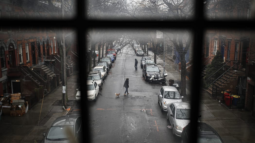 A pedestrian walks their dog through a quiet street, Tuesday, March 17, 2020, in the Brooklyn borough of New York. As of Sunday, nearly 2,000 people with the virus have been hospitalized in the state of New York, and 114 have died, officials said. More than 15,000 have tested positive statewide, including 9,000 in New York City.  (AP Photo/John Minchillo)
