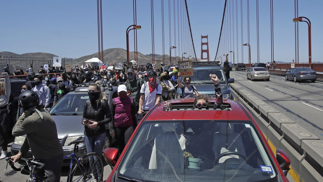 A motorist raises her fist through the sunroof of her car while marchers walk past as traffic is stopped on the Golden Gate Bridge in San Francisco, Saturday, June 6, 2020, at a protest over the Memorial Day death of George Floyd. Floyd died May 25 after being restrained by Minneapolis police. (AP Photo/Jeff Chiu)