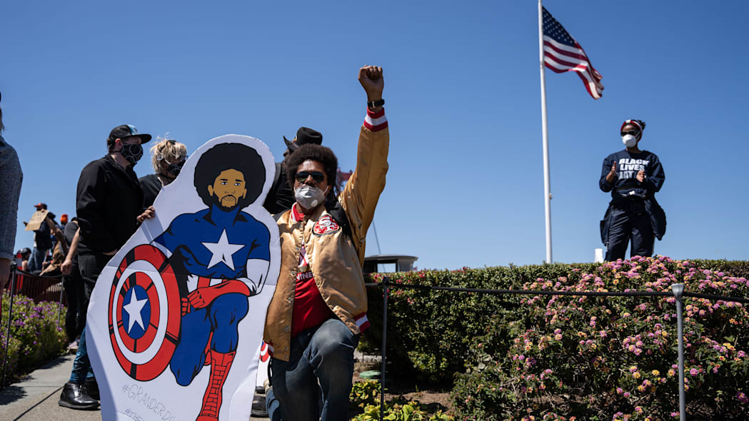 TOPSHOT - A protester kneels with a cardboard cut-out of Colin Kaepernick in Captain America costume in front of a US flag near the Golden Gate Bridge during a demonstration against racism and police brutality in San Francisco, California, on June 6, 2020. - Demonstrations are being held across the US following the death of George Floyd on May 25, 2020, while being arrested in Minneapolis, Minnesota. (Photo by Vivian LIN / AFP) (Photo by VIVIAN LIN/AFP via Getty Images)